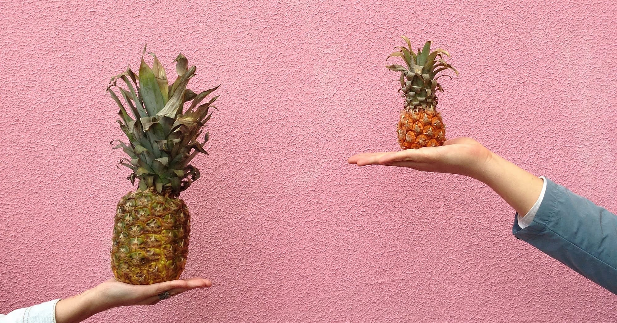 Two people holding fruit for comparison