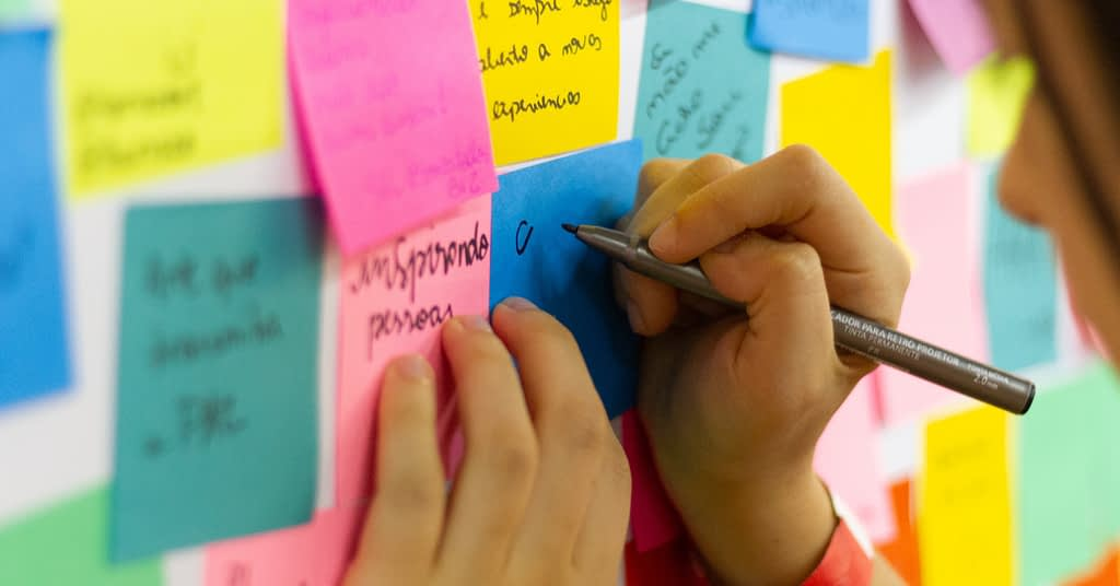Someone drawing on colorful sticky notes